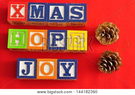 Xmas Hope and Joy spelled with Alphabet blocks and two acorns on a red background