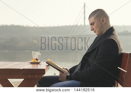 Young handsome man sitting in an outdoor cafe by the river drinking tea and reading a book on a sunny autumn day