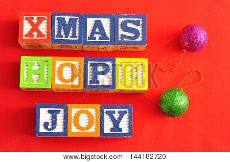 Xmas Hope and Joy spelled with Alphabet blocks and two baubles on a red background