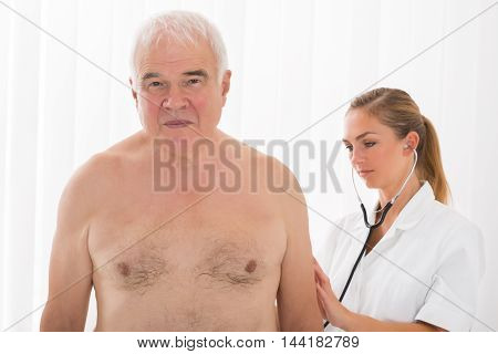 Female Doctor Examining Senior Male Patient's Back With Stethoscope