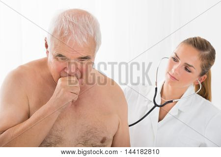 Young Female Doctor Using Stethoscope On Senior Male Patient's Back