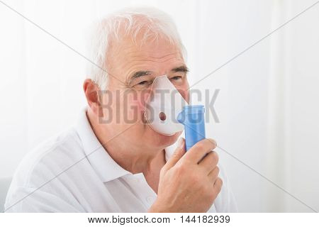 Close-up Of A Senior Man Inhaling Through Oxygen Mask In Clinic