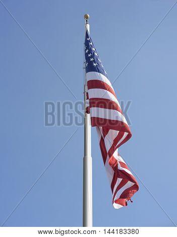 American flag on the pole against blue sky