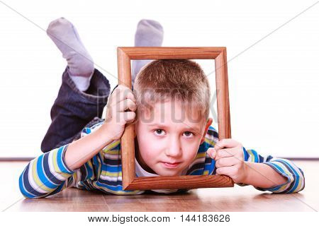 Spending free time and have fun. Playful little boy play with empty picture frame show face lie on floor.