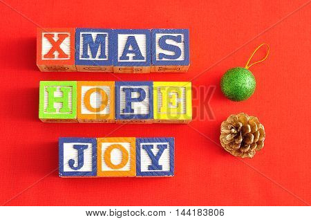 Xmas Hope and Joy spelled with Alphabet blocks and an acorn and bauble on a red background
