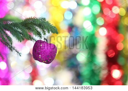 Closeup of blue fruit bauble hanging from a decorated Christmas tree