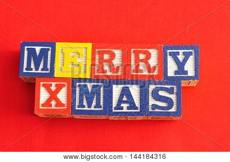 Merry Xmas spelled with Alphabet blocks on a red background
