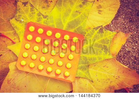 Pill package on leaf. Pack of pills lying on maple leaves. Nature vegetation health medicine concept.