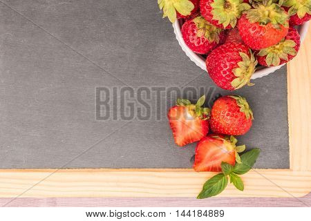 Fresh strawberries in bowl on slate. Top view with copy space