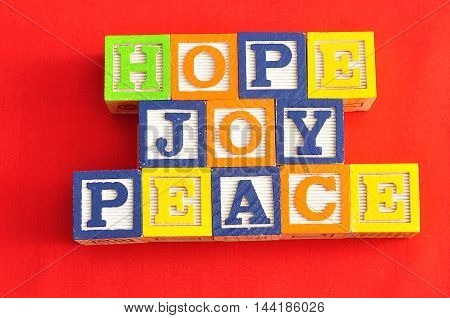 Xmas Hope and Joy spelled with Alphabet blocks on a red background