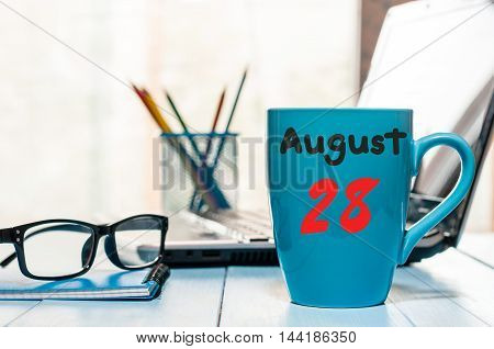 August 28th. Day 28 of month, hot cup with drink and calendar on hard worker workbench background. Summer time. Empty space for text.