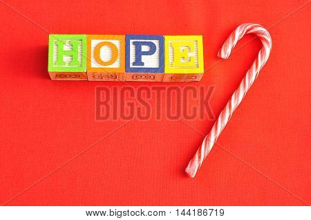 Hope spelled with Alphabet blocks on a red background with a candy cane