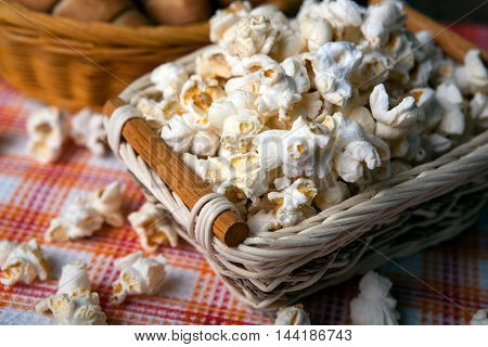 salted popcorn in a wicker basket on a napkin close up