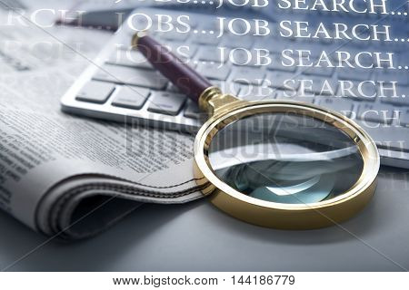 inscription job search and a magnifying glass on newspaper and keyboard