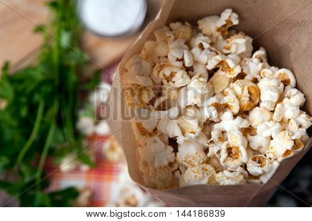 fresh salted popcorn in a paper bag close up