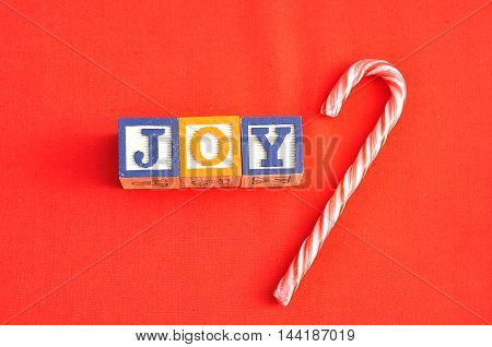 Joy spelled with Alphabet blocks on a red background with a candy cane