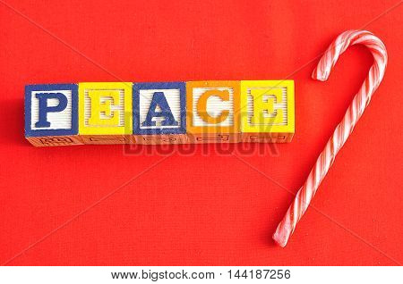 Peace spelled with Alphabet blocks on a red background with a candy cane