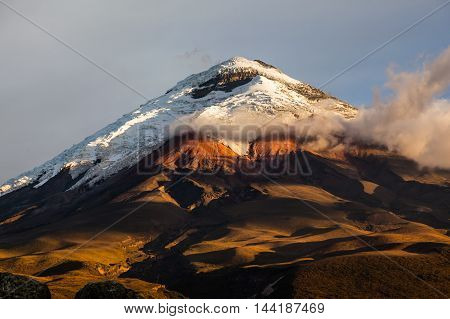 Cotopaxi volcano illuminated by the last rays of setting sun