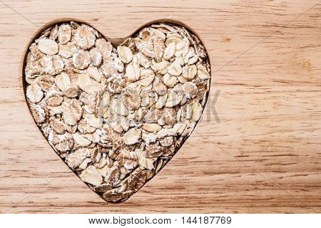Dieting healthcare concept. Oat cereal oatmeal heart shaped on wooden surface. Healthy food for lowering cholesterol.