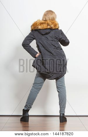 Back view of young fashionable girl wearing jacket with hood. Fashion in winter time. Standing in stride.