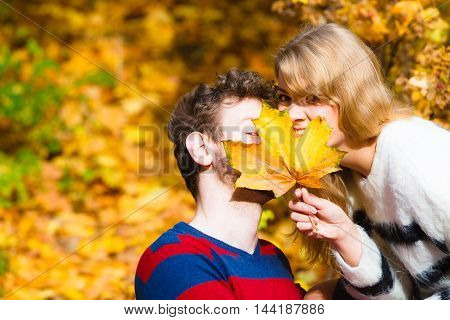 Couple With Maple Leaf Kissing In Autumn Park