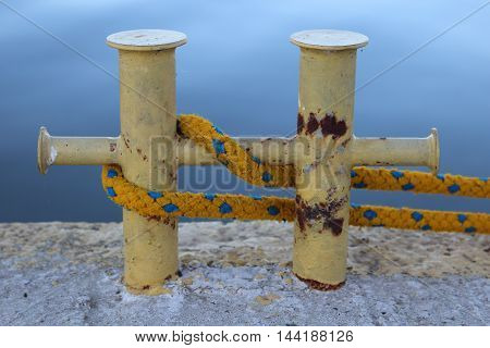 the bollard with a yellow rope in port