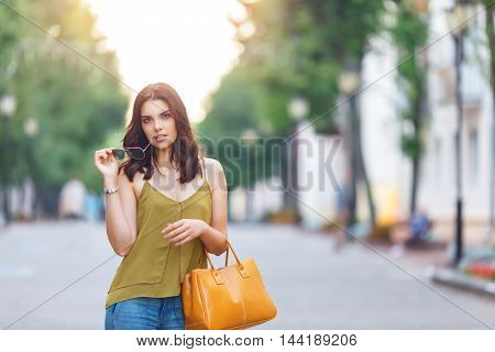 Fashion city portrait of stylish hipster woman, natural dress, makeup, long brunette hairs, walking alone at weekend, enjoy vacation in Europe, modern trendy summer outfit. Evening soft sunlight