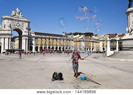 LISBON, PORTUGAL - September 30, 2015: Busker performing with soap balloons in the middle of Commerce Square the main Lisbon public square on September 30, 2015 in Lisbon, Portugal