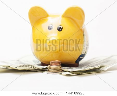 Yellow piggy bank and Stack of money coins isolated over the white background lot dollar cash under it