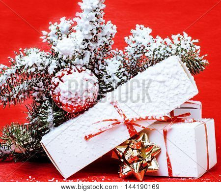christmas decoration , red background with snow for post card greetings, toy design on tree macro xmas gifts under santas hat