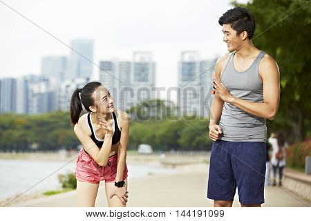 asian man and woman runner jogger saying hello to each other in a city park.