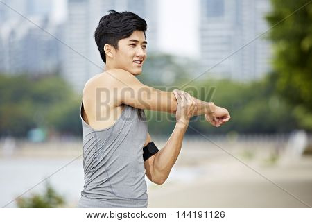 young asian man warming up by stretching arms before exercise.