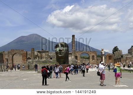 POMPEII ITALY - may 25 2016: tourist in famous antique ruins of town Pompeii Italy. Pompeii was destroyed and buried with ash and pumice after eruption in 79 AD. mont vesuvius in background