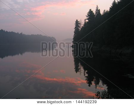 Hazy reflection of a pink sunrise on the lake.