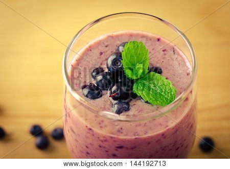 Healthy blueberry banana smoothie with mint and fresh berries in a glass on a rustic table