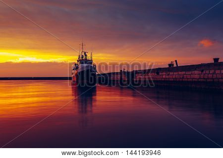 Harbor and boat under a colorful sunset.