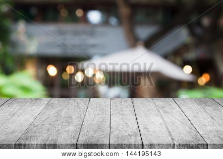 Perspective grey wooden table top with cafe blurred abstract background