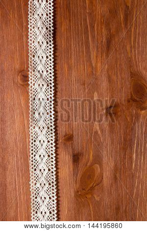 Openwork lace on the wooden surface. Background for creativity.