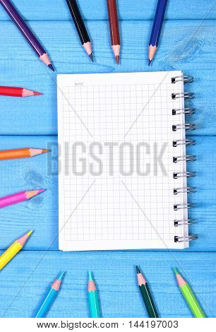 Colorful Crayons And Notepad On Blue Boards, School Accessories, Copy Space For Text