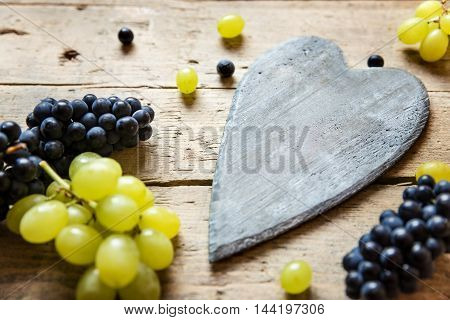 White And Blue Grapes And A Wooden Heart With Copyspace