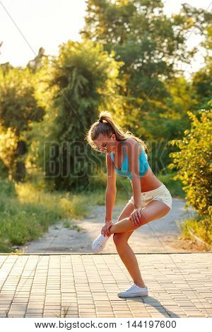 Young slim woman doing stretching hamstring in a city park. Outdoors Sports. Healthy lifestyle concept. Morning exercises