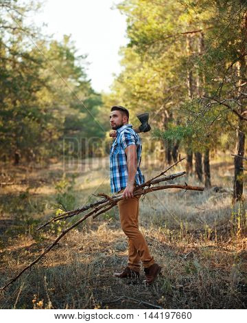 Lumberjack with an ax and firewood goes through woods. Woodcutter in plaid shirt chopped wood for the fire. Felling trees. Logging. Manual labor.