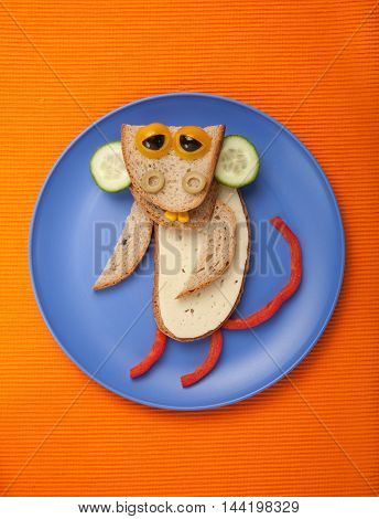 Amusing monkey made of bread cheese and vegetables on plate and fabric