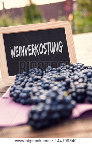Lots Of Black Grapes And Slate With German Word