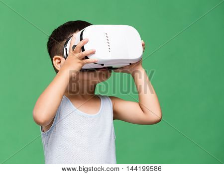 Asian boy watching though VR device