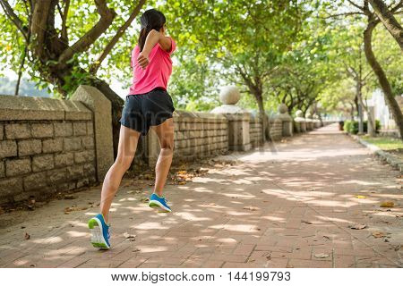 Back view of woman running in a park
