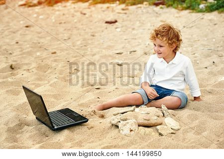 a boy plays on the beach , lying next to the laptop