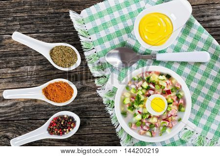 meat greens and vegetables cold summer soup with serum and yogurt sprinkled with parsley and spring onion in white cup with spices and mustard in gravy boat on old rustic boards view from above