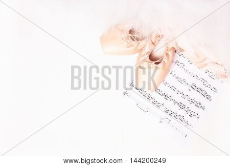 Ballet shoes skirt and music sheet on a white background
