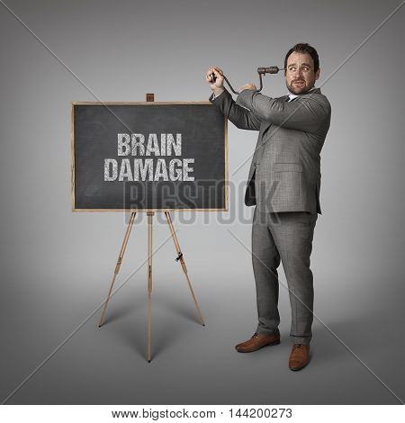 Brain damage text on blackboard with businessman drilling his head